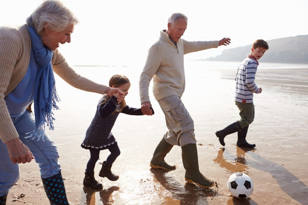 grandparents playing soccer with children on beach