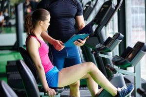 Fitness trainer explaining in gym