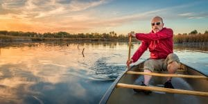 senior paddling canoe