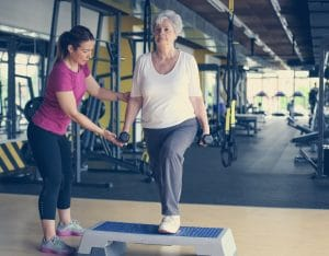 Personal trainer working exercise with senior woman in the gym.