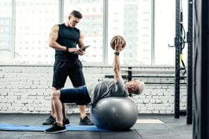 senior man working with personal trainer