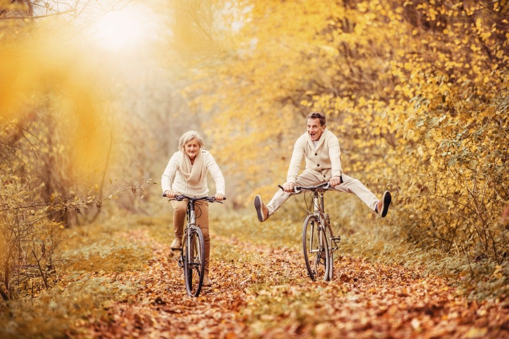 senior couple biking in autumn