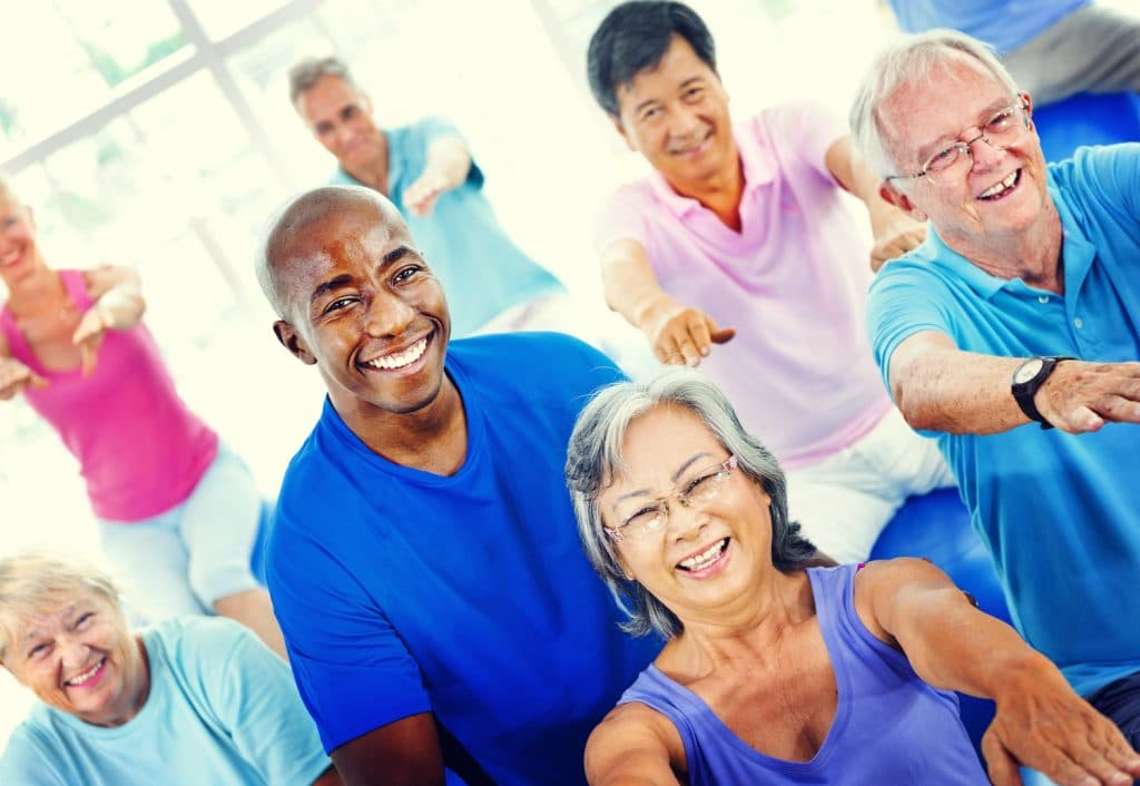 group of happy mature adults exercising