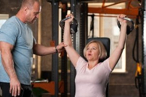 Personal trainer man corrects exercises of older pretty woman