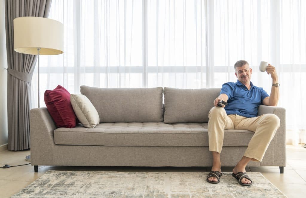 middle aged man sitting on a sofa and watching TV