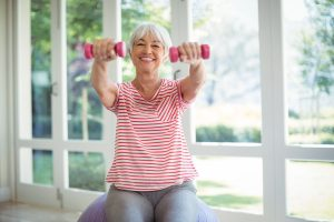 older woman lifting dumb bells