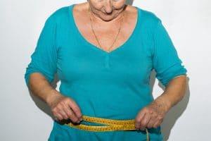 older woman measuring waist girth