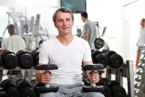 mature man with dumb bells in the gym