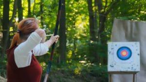woman aiming arrow at target
