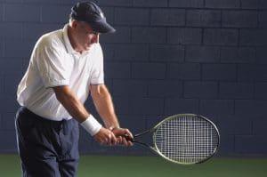 older man swinging tennis racquet
