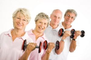 group of four older adults lifting dumb bells