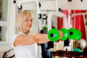 mature woman lifting green dumb bells