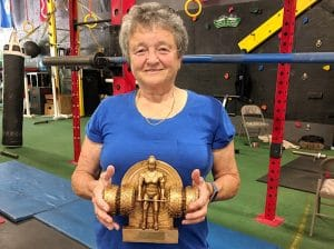 older woman with weightlifting trophy